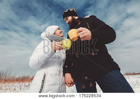 Girl and boyfriend enjoy tea drinking, standing in winter field. The concept of a winter hike, camping, tourism, holiday and vacation