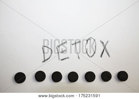 Activated charcoal absorbent black pills and insription Detox written by it