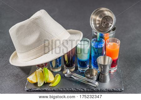 six different colored shot drinks lined up on a black stone plate ice cubes in shaker and ice tongs lemon and lime white hat party set