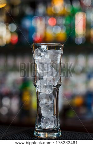 Highball glass with ice standing on bar counter in nightclub