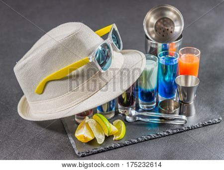 six different colored shot drinks lined up on a black stone plate ice cubes in shaker and ice tongs lemon and lime white hat yellow sunglasses party set