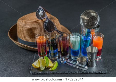 six different colored shot drinks lined up on a black stone plate ice cubes in shaker and ice tongs lemon and lime brown hat brown sunglasses party set