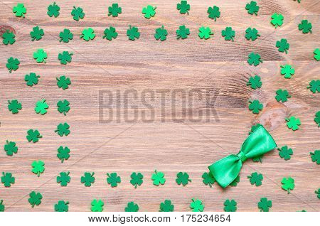 St Patrick's Day background - green quatrefoils and bow tie on the wooden background with space for text. St Patrick's Day background with clover leaves. St Patrick's Day concept with St Patrick's Day symbols
