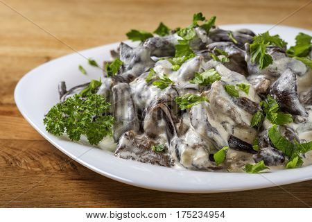 Romanian food - mushrooms with sour cream and parsley on plate