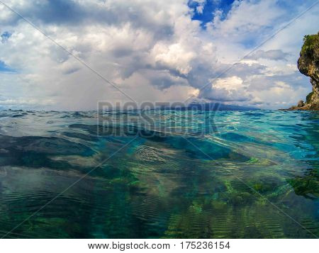 Marine landscape with transparent water and blue sky. Blue sea water look through. Double seaview above and below waterline. Clean water of tropical seashore. Beach day in tropic paradise lagoon photo