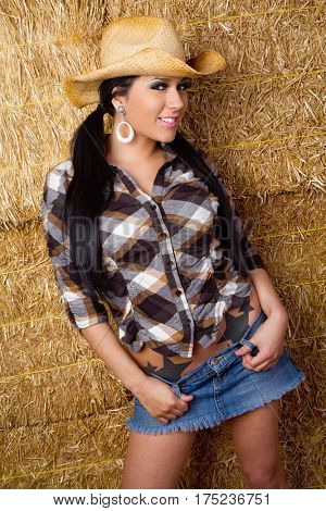 Pretty smiling cowgirl in hay