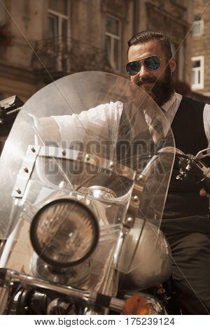 Serious Hipster Bearded Biker Man in black jacket sitting on motorbike outdoors
