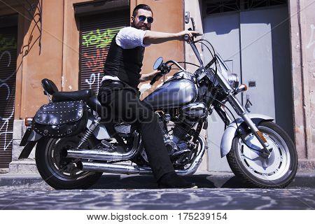 Serious Bearded Biker Man sitting on motorbike outdoors