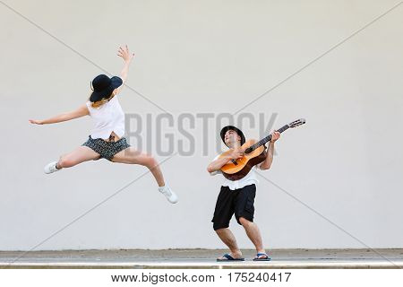 Relationship goals concept. Couple on romantic date. Man playing guitar and woman having fun jumping