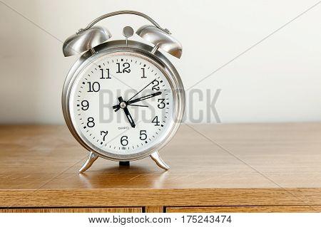 Alarm clock stands on a dresser .