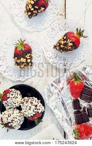 Variety of strawberries covered with a dark chocolate with different toping - nuts pistachios coconut and white chocolate chips. Homemade gourmet dessert for Valentine's Day. Top view.