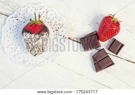 Strawberrie covered with a dark chocolate with coconut on the white wooden table. Homemade choco dipped berry. Gourmet summer dessert. Top view.
