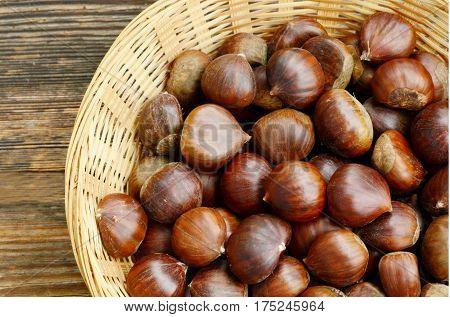 Castanea sativa or sweet chestnut in the basket on wooden background.