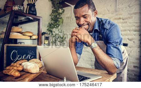Adult Man Using Laptop in Bakery Shop