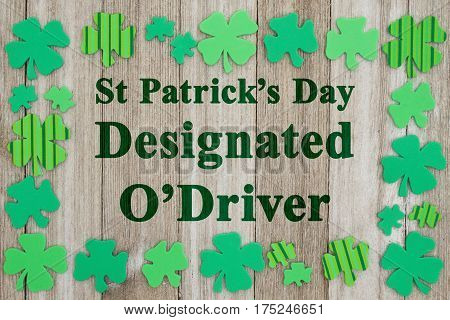 Saint Patrick's Day safety message Green shamrocks on weathered wood with text St Patrick's Day Designated O'Driver