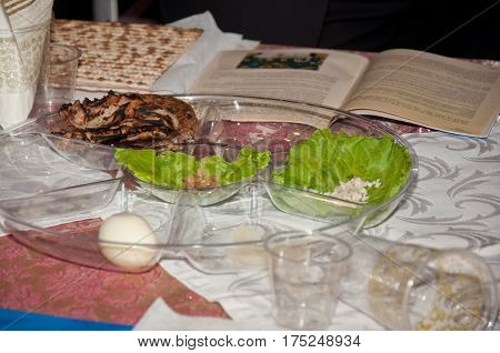 Passover traditional meal with matzo egg salad lay on transparent plate near book. Jewish traditions