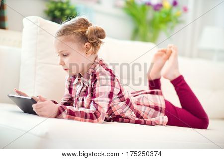 Pretty Little Child Girl  Using A Digital Tablet, Looking And Smiling While Lying On The Whitw Couch