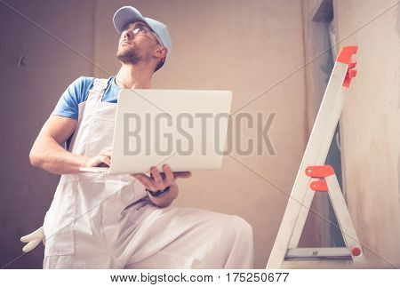 Caucasian Construction Worker with Laptop Managing Remodeling Project.