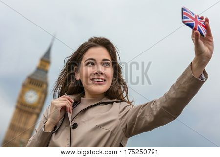 Girl or young woman tourist on vacation taking a selfie photograph by Big Ben with Union Jack cell phone, London, England, Great Britain