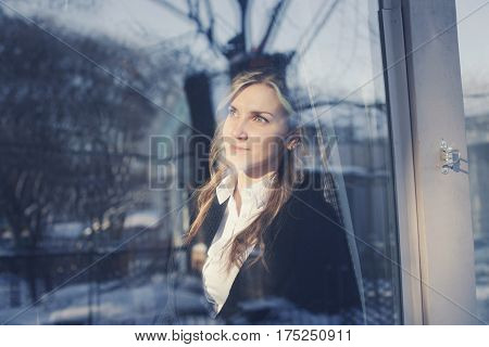 Happy Young Girl Looking Through A Window.