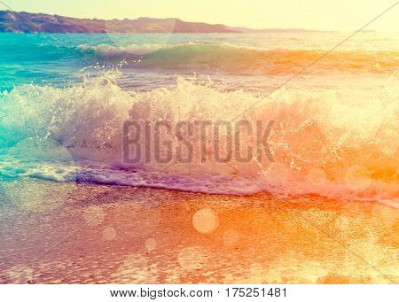 Waves breaking on a beautiful sandy beach on the shore of the mediterranean coast. Vintage stylized photo with light leaks and bokeh effect.