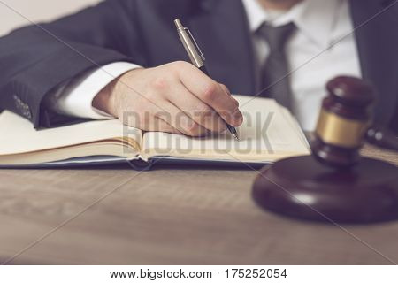 Detail of a judge sitting at his desk studying new laws and legislation and writing notes. Selective focus