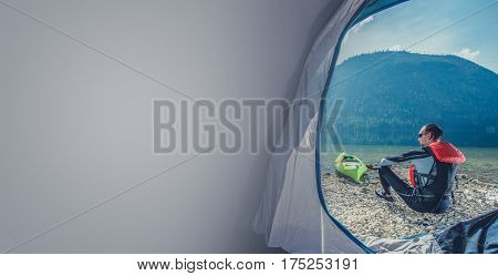 Scenic Lake Shore Camping with Kayak. Caucasian Sportsman in the Wetsuit Preparing For Kayak Trip. Photo with Copy Space.