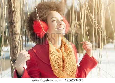 Happy Young Woman With Warm On Ears Enjoying Winter Sunshine