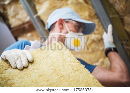 Mineral Rock Wool Insulating Concept Photo. Worker with Piece of Insulating Wool in Hands.