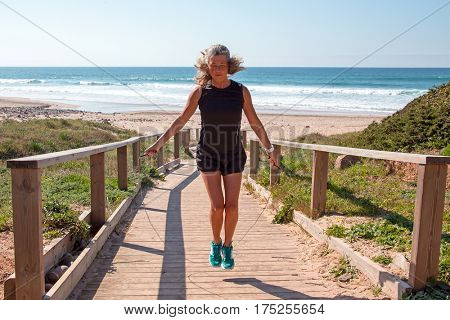 Mature woman exercising jumping rope high knees at the beach