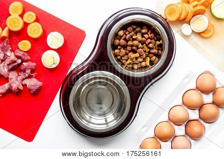 Dry dogfood, eggs, raw meat, fresh carrot and courgette on kitchen table background top view