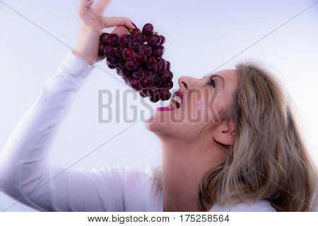 A Blonde Woman Eating Red Seedless Grapes