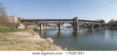 Pavia Italy - March 8 2015: Covered bridge over the river Ticino. Very quaint has five arches and is completely covered with two portals at the ends and a small chapel religious center.