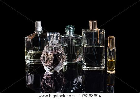 Different perfume bottles with reflections on black background with space for text. Perfumery, cosmetics, fragrance collection