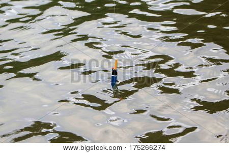 Fishing float in water. Rippled water of forest lake. Fishing weekend concept photo. Waiting for fish to nibble. Fishing with rod image. Fishing tackle in water. Active holiday outdoor hobby picture