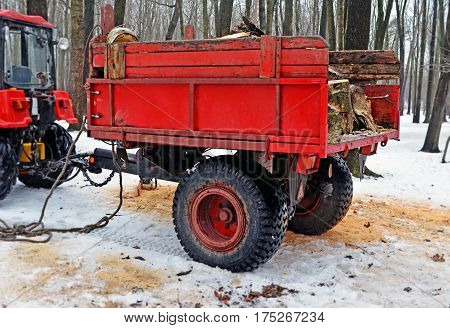 Red trailer with firewood attached to the tractor in the winter in the wood or the park. Side view.