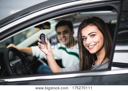 Beautiful Young Couple Sitting At The Front Seats Of Their New Car While Woman Showing Keys And Smil