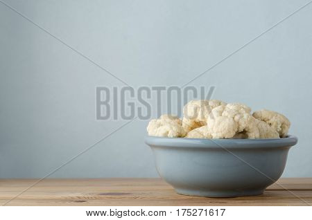 Raw Cauliflower In Bowl On Wood Plank Table With Blue Background