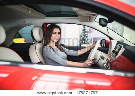 Driving around city. Young attractive woman smiling and looking at camera while driving a car