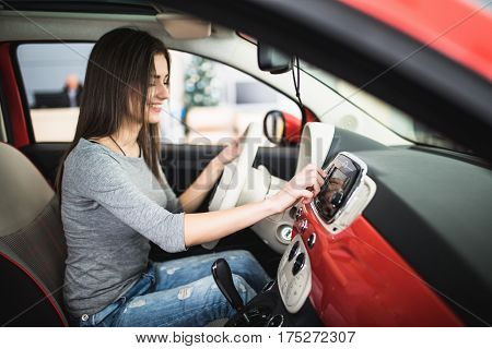 Car dashboard. Radio closeup. Woman sets up radio