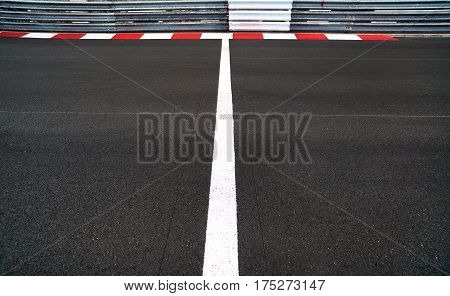 Start and Finish motor race line asphalt on Grand Prix street circuit. Red and white curb guard rail or guardrail on background