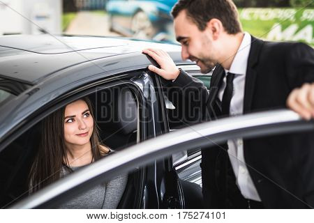 Beautiful young woman buys a car in the dealership saloon in showroom