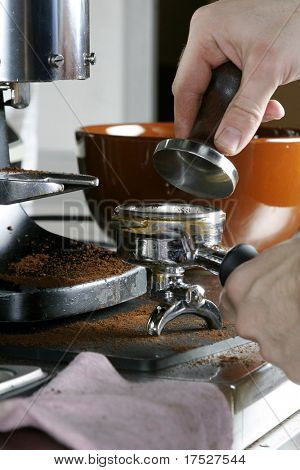 Tamping the espresso after dosing and leveling