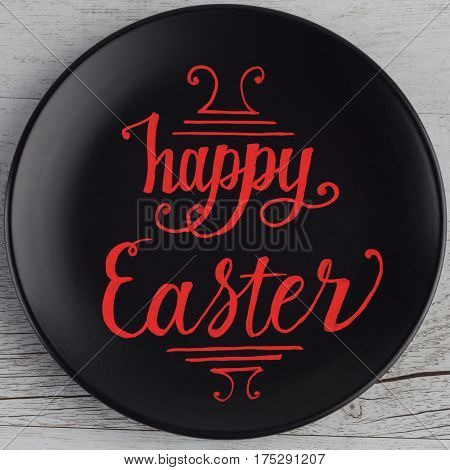 Happy Easter Hand Lettering Written In Red On Black Plate And White Wood Background. Square Image.