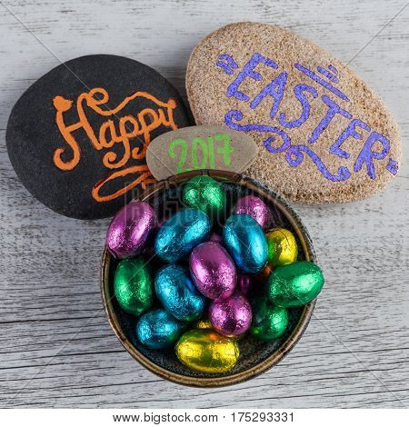 Happy Easter 2017 Lettering Written On Pebbles With Chocolate Eggs Wrapped In Colorful Foil. Square