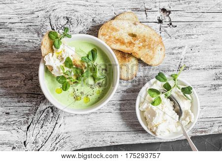 Green peas cream soup and cheese toast on the light wooden table top view