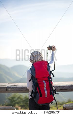 Hiker woman take a photo on the mountain background blue sky Thailand