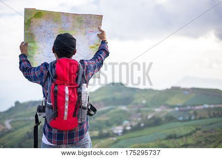 Lost hiker with backpack checks map to find directions in wilderness area