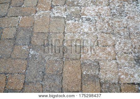 winter ice melting salt on the brick ground