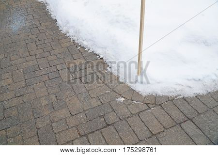 brick sidewalk with snow removal in winter
